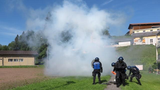 Polizisten vor einer Rauchwolke.