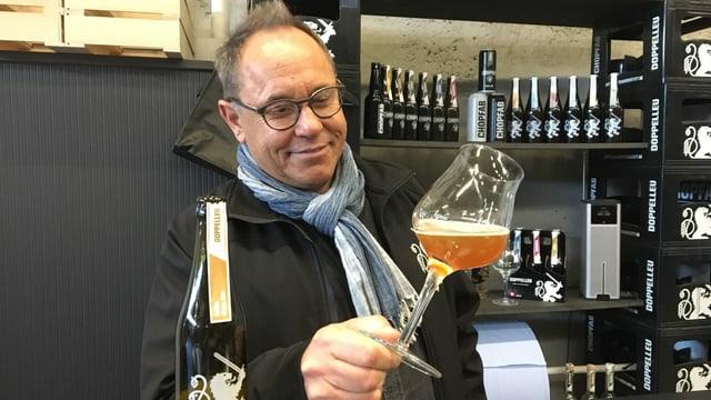 Ein Mann mit Brille hält ein Glas Bier schräg in der Hand