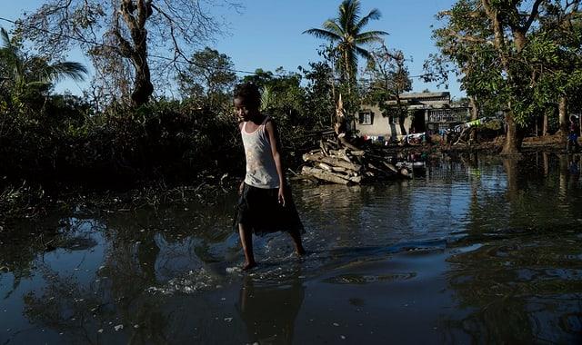 Purtret d'in uffant che passa tras aua che las inundaziuns han purtà.