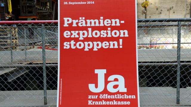 Rotes Ja-zur-öffentlichen-Krankenkasse-Plakat steht an einen Maschendrahtzaun angelehnt.