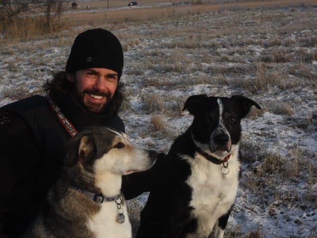 Olaf Thalmann mit zwei Hunden auf einem Feld.