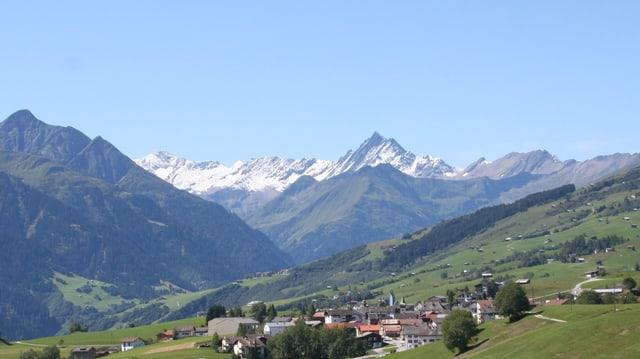 Das Dorf Lugnez von weitem, im Hintergrund verschneite Berge.