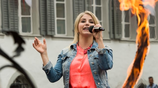 Blonde Frau singt ins Mikrophon und hat rote Bluse an