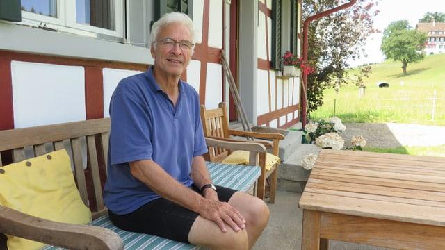 Seniore Hubert Lombard sitzt vor seinem Bauernhaus.