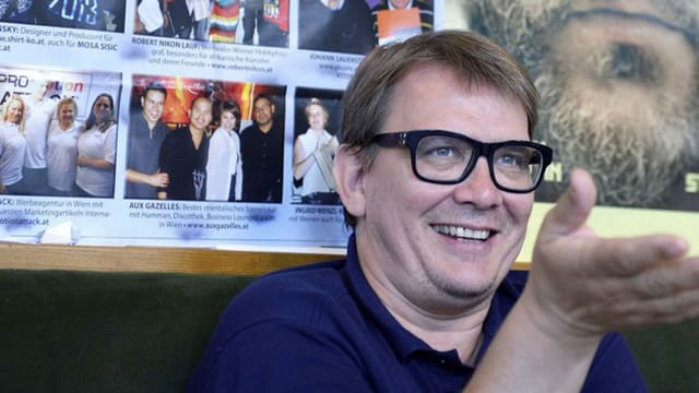 Sven Regener sitzt vor einem Plakat und ist lachend in ein Gespräch vertieft.