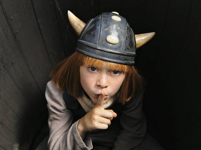 Wickie, mit roten Haaren und Wikingerhelm, beugt sich nach vorne und legt den Finger auf seine Lippen.