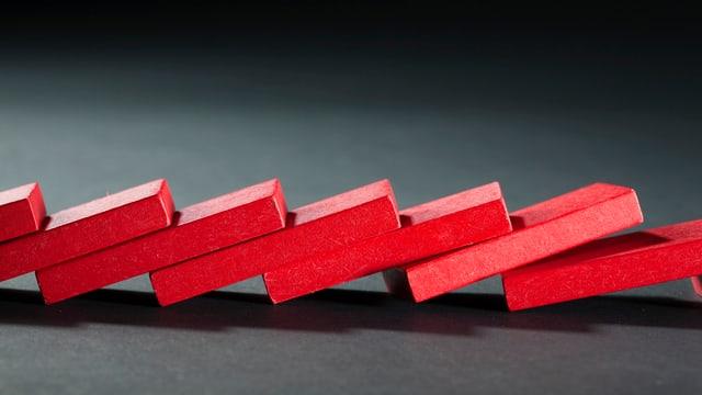 Reihe rote Dominosteine, die umgefallen ist.