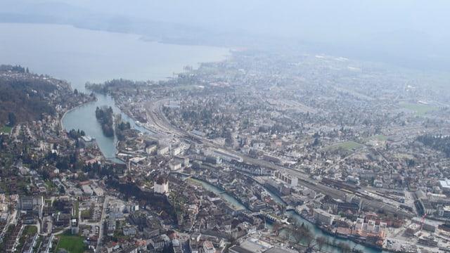 Luftaufnahme der Stadt Thun mit See.