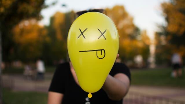 Eine Person hält einen Luftballon, auf dem ein Gesicht mit heraushängender Zunge gezeichnet wurde.