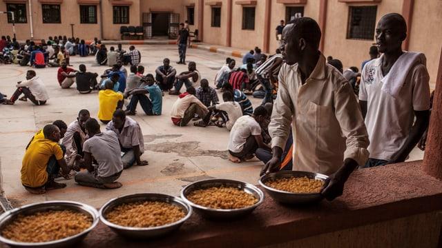 MIgranten in einem Gefangenlager verteilen Essen.