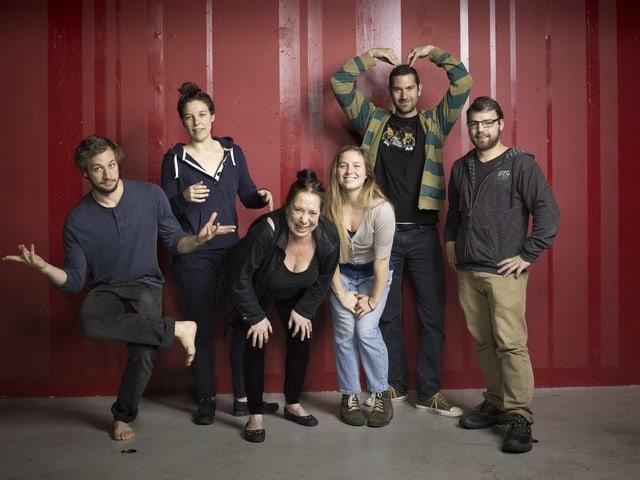 Sechs personen stehen vor einer weinroten Wand. Alle machen eine eigene Bewegung, gehen in die Knie oder strecken die Arme aus. Es ist das neue Mummenschanzensemble, drei Frauen und zwei Männer und ein Lichttechniker.