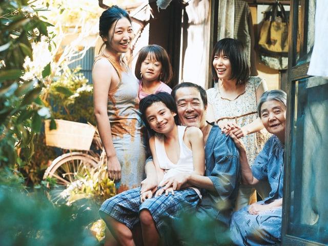 Eine sechsköpfige Familie sitzt lachend vor einem Haus