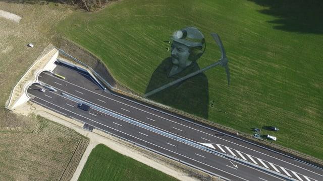 Porträt eines Tunnelarbeiters in der Wiese neben der Autobahn.