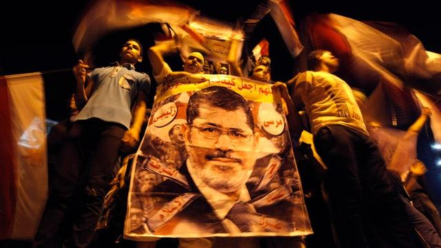 Anhänger von Mursi mit einem Plakat