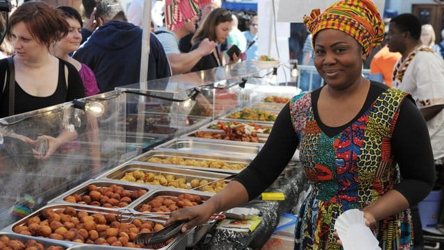 afrikanische Frau in farbigem Gewand schöpft Essen an einem Stand