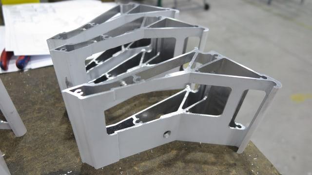 Metallformen, die in einer Fabrik auf einem Tisch liegen.