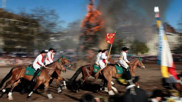 Pferde mit Reitern im Gallopp vor brennendem Scheiterhaufen