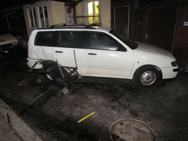 Ein weisses Auto am Strassenrand, die Hinterseite komplett ausgedrückt.