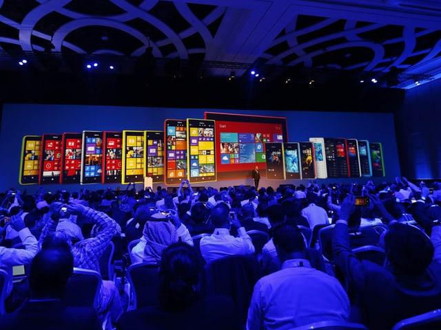Eine Menschenmenge sitzt im Dunkeln vor einem riesigen Bildschirm, der Bilder von neuen Tablets zeigt.
