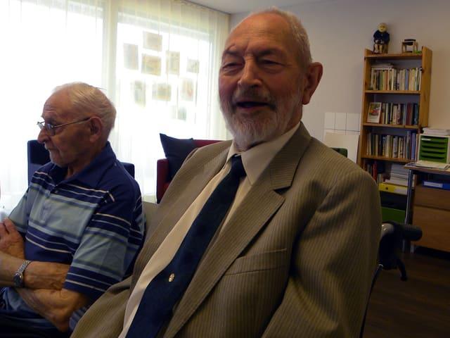 Zwei ältere Männer sitzen in einem Zimmer mit grossen Fenstern an einem Tisch.