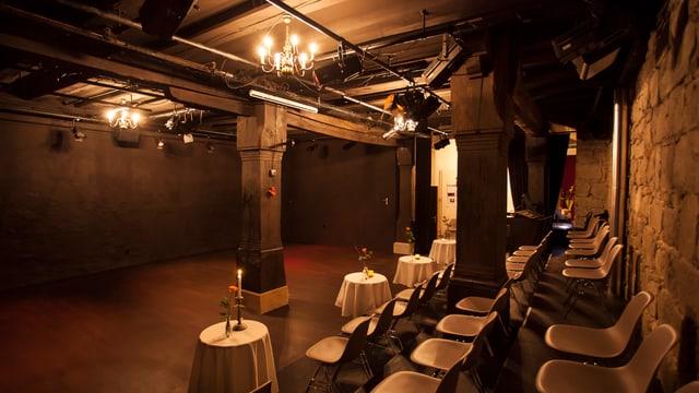 Ein dunkler Raum, auf der rechten Seite Stühle. An der Decke hängt ein Leuchter.