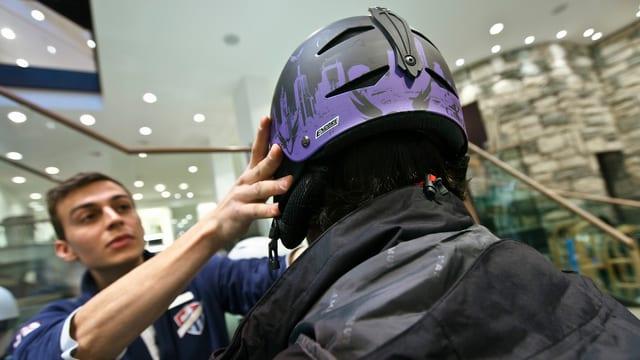 Einem Mann wird in einem Wintersportgeschäft ein Ski-Helm aufgesetzt.