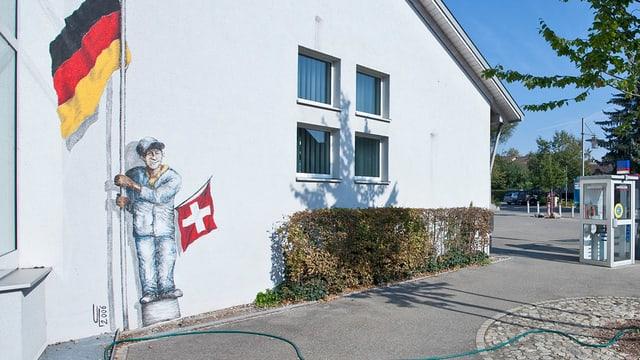 Eine Hausfassade, ein Mann aufgemalt, der eine grosse Deutschlandfahne und eine kleine Schweizfahne hält.