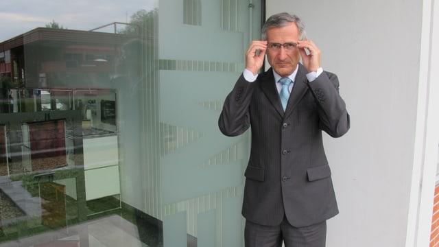 Gian-Luca Bona, Direktor der Empa, im grauen Anzug, rückt vor dem Glas-Eingang der Empa seine Brille zurecht.