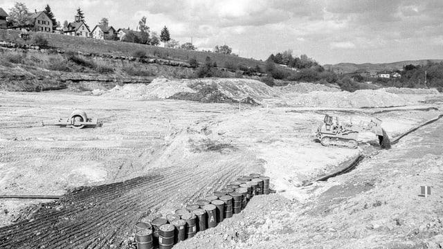 Grosse Grube mit Fässern und Bagger, historische Aufnahme