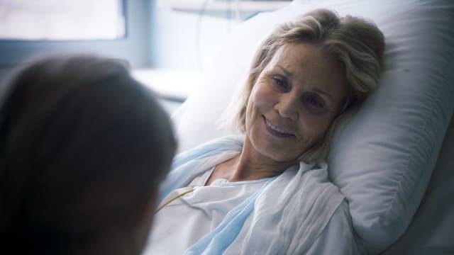 Eine kranke Frau liegt im Krankenhaus-Bett.