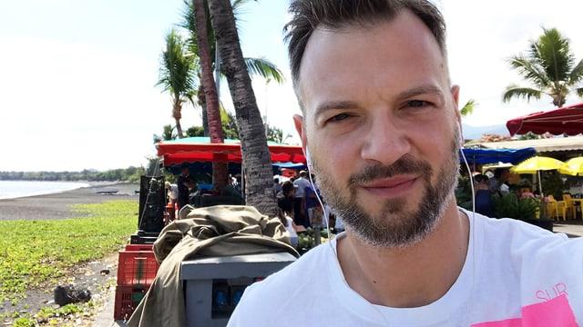 Jüngerer Mann mit Bart, im Hintergrund Palmen und ein Traktor.