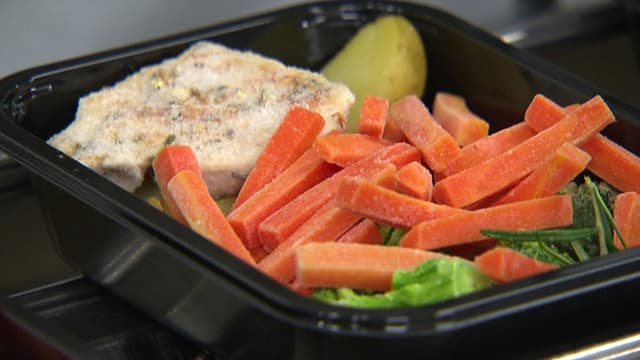 Ein Fertiggericht mit Gemüse und einem Stück Fleisch.