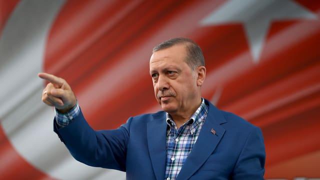 Erdogan mit erhobenem Zeigefinger vor einer türkischen Flagge.