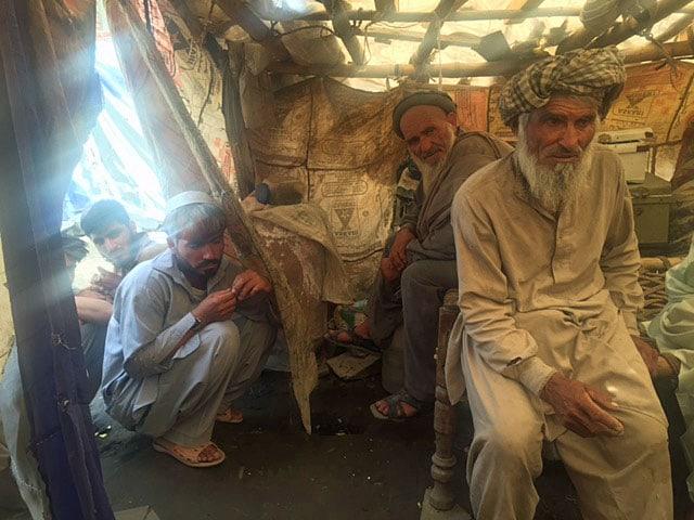 Vier afghanische Flüchtlinge sitzen unter Plachen in einem Zelt. Sie tragen alle Bärte und Gewänder.