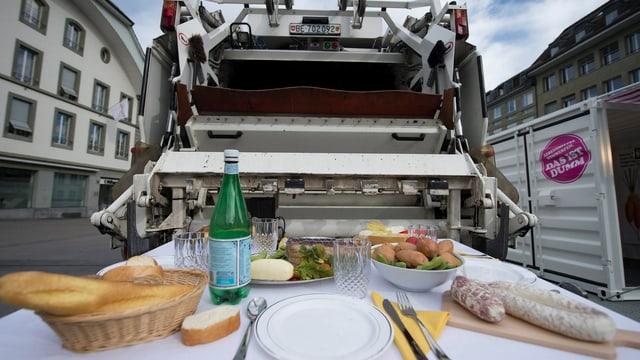Ein Tisch mit Lebensmitteln, dahinter ein Müllabfuhrwagen.