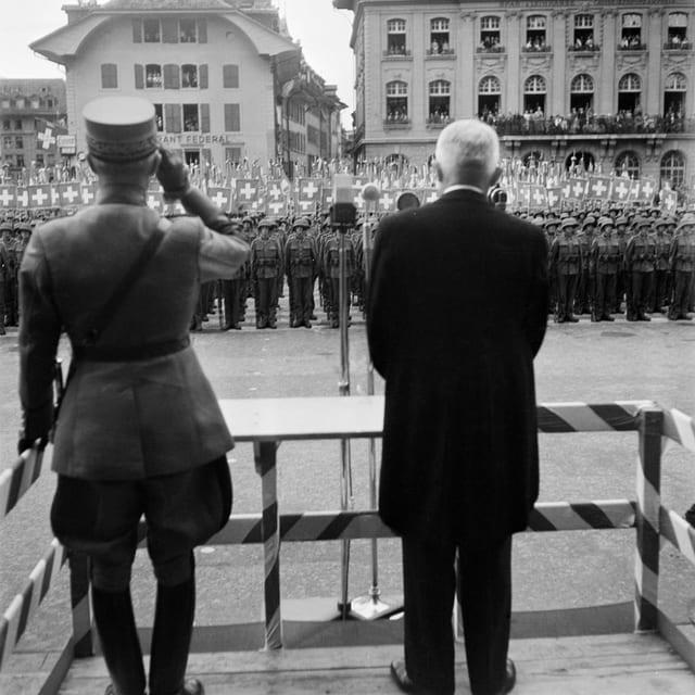 Blick von hinten auf General Henri Guisan auf dem Berner Bundesplatz. Vor ihm stehen viele Soldaten in Reih und Glied.