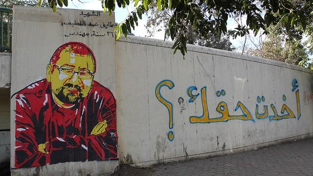 Abbildung eines Graffitos auf einer Mauer: Portrait eines Mannes mit Brille und Bart, der die Arme vor dem Körper verschrämkt hält.