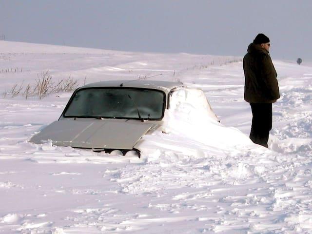 Die grossen Schneeverwehungen haben ein Auto komplett blockiert. Ein Mann steht vor dem Auto und starrt in die kalte Winterlandschaft.