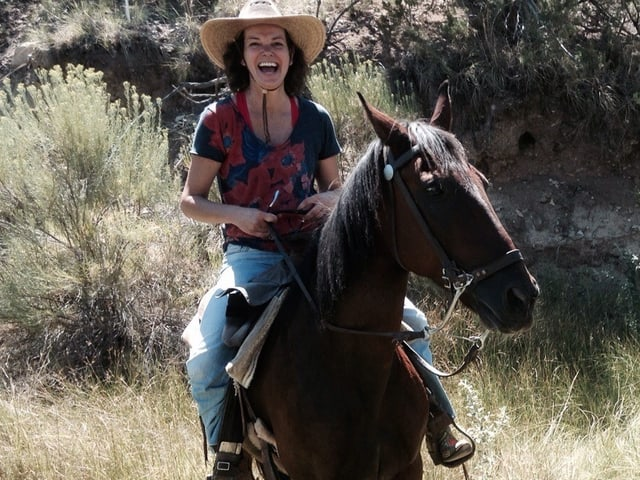 Milena Moser mit Cowboyhut auf einem Pferd.