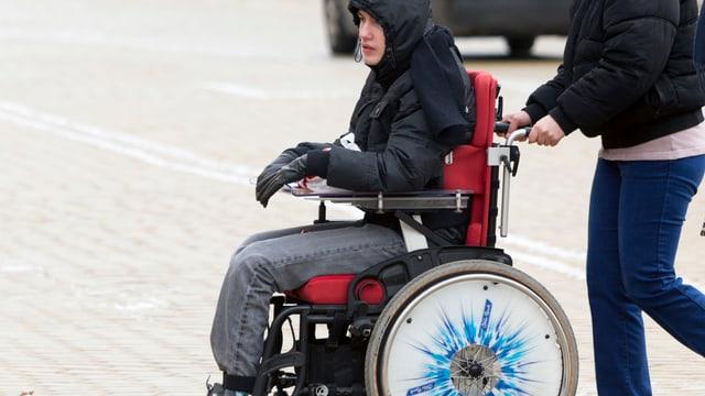 Junge im Rollstuhl wird geschoben