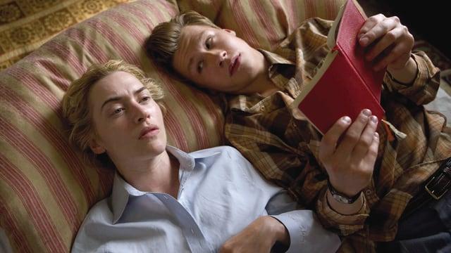 junger Mann liest einer Frau vor - sie liegen nebeneinander