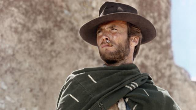 Ein Mann mit Hut, Poncho und Zigarette.
