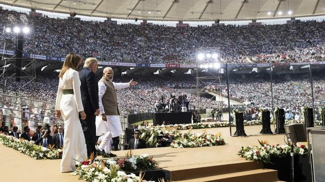 Donald und Melania Trump sowie Narendra Modi betreten die Bühne in einem voll besetzten Stadium.