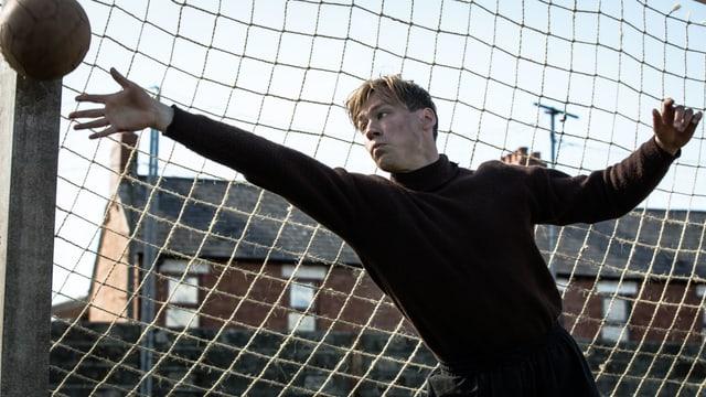 Ein junge im Tor. Er hält einen Ball.