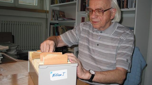 Der Journalist Roman Bussmann blättert in einem Karteikasten.