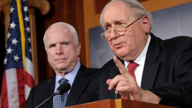 McCain und Levin an einem Rednerpult vor einem Mikrofon, links neben ihnen eine US-Flagge.
