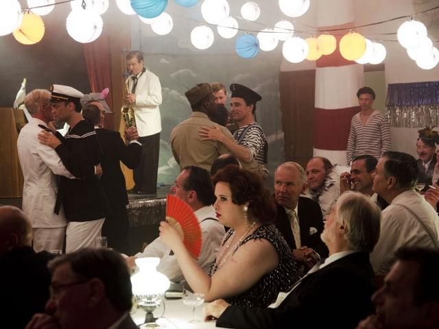 Leute tanzen, ein Mann spielt Saxophon auf der Bühne, Lichter an der Decke.