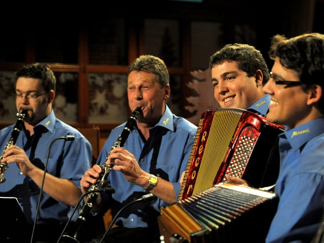 Vier Volksmusikanten in blauen Hemden.