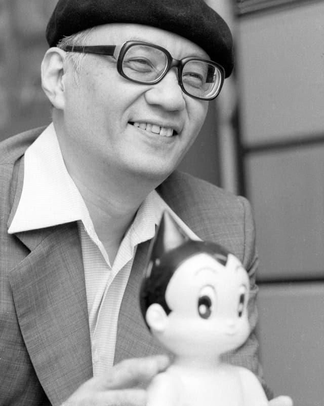 Der lächelnde Osamu Tezuka mit Beret und Brille in einer schwarzweiss Aufnahme, vor ihm steht eine «Astroboy»-Figur.