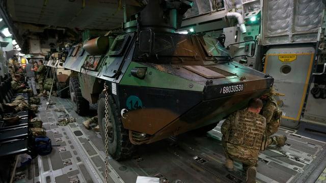 Soldaten befestigen einen Panzer in einem Flugzeug.